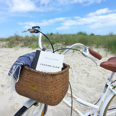 Close-up view of a bicycle basket with a book and a blanket inside, on the beach