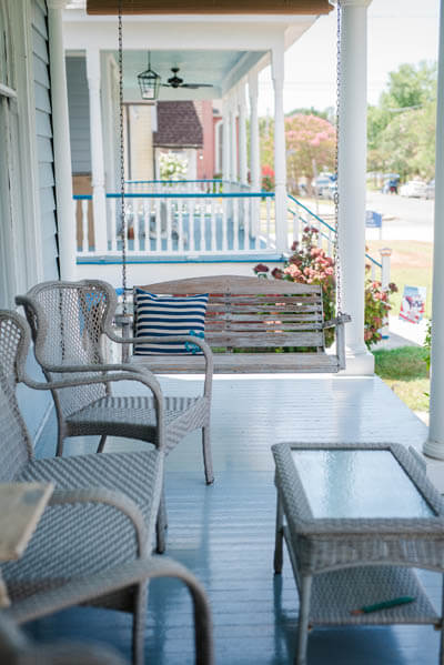 Decorated porch swing, chairs and table on a veranda