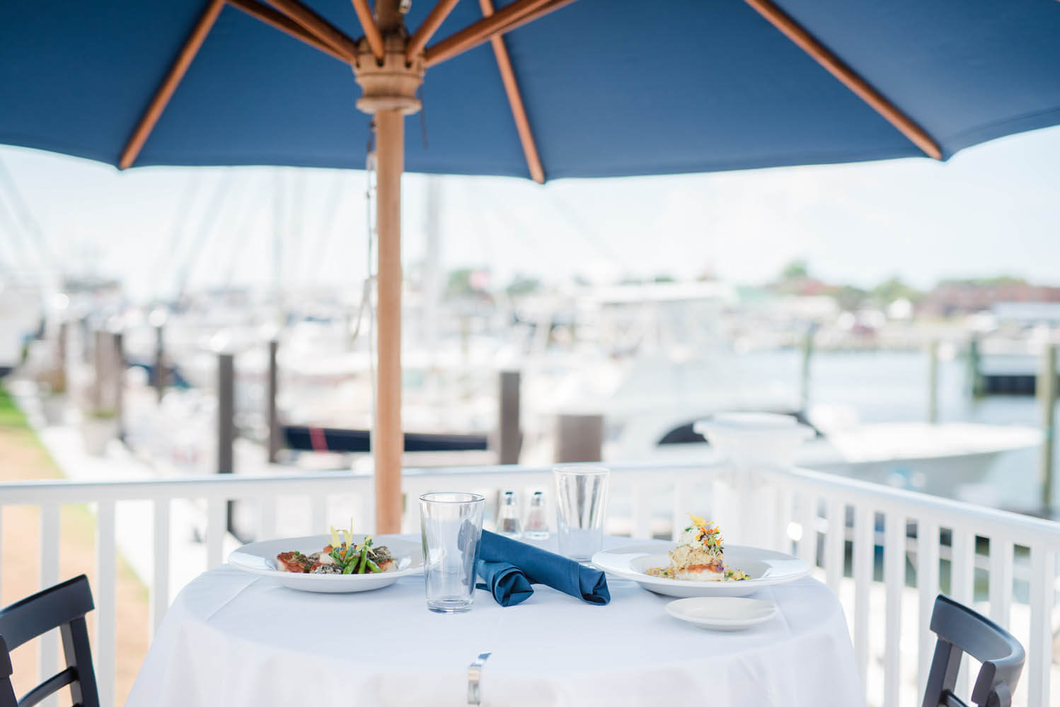 Close up of a restaurant table with two dishes, with harbor in background