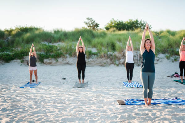 Group of women doing yoga at a beach
