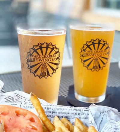 Close-up view of two glasses of beer and a plate of French fries