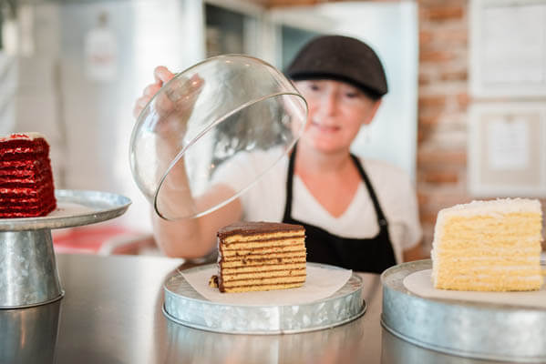 Female pastry chef in front of three pieces of cake placed on cake holder