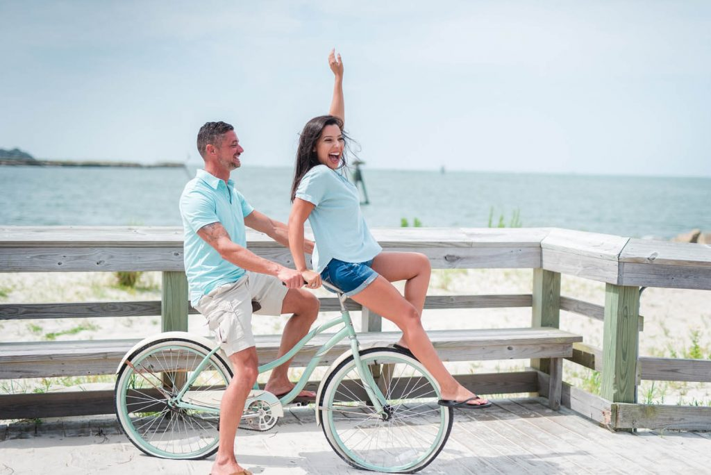 Happy couple on a bike at beachfront