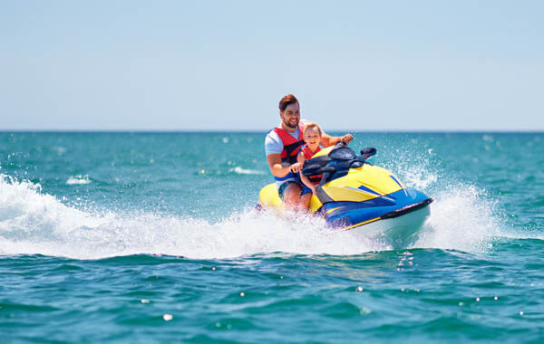 Man and little boy riding a jet ski on the sea