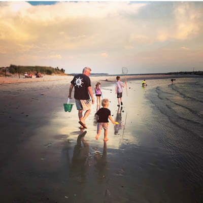 Man and children playing together at the beach