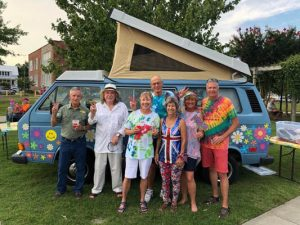 Lovefest group photo of people standing in front of a painted van, wearing colorful clothes