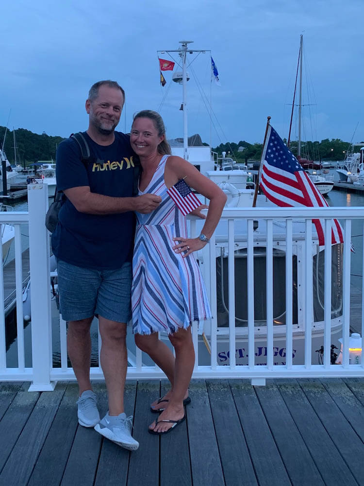 Couple posing at harbor with US-flag in hand