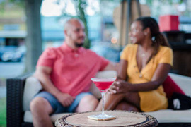 Close-up view of a cocktails placed on a table, woman and man chatting in background